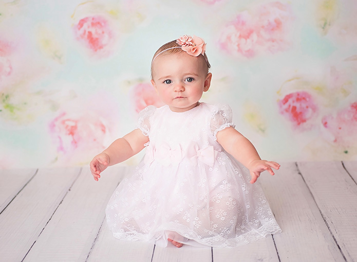 6 month old girl in pink dress against floral backdrop