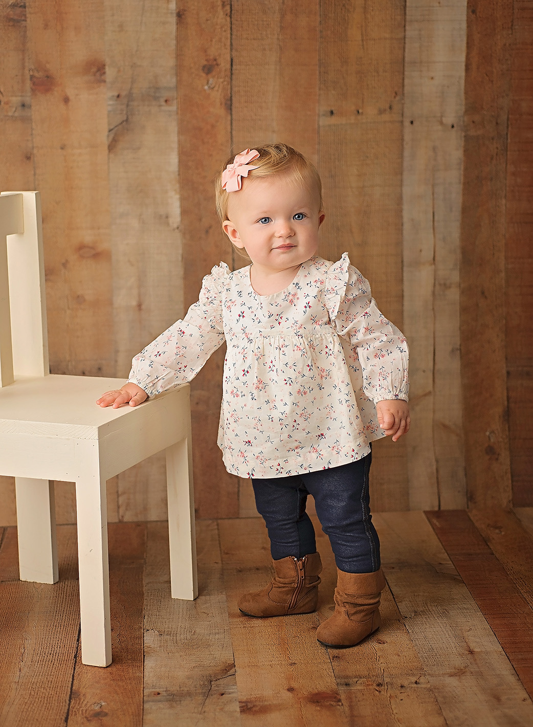 one year old girl standing by chair