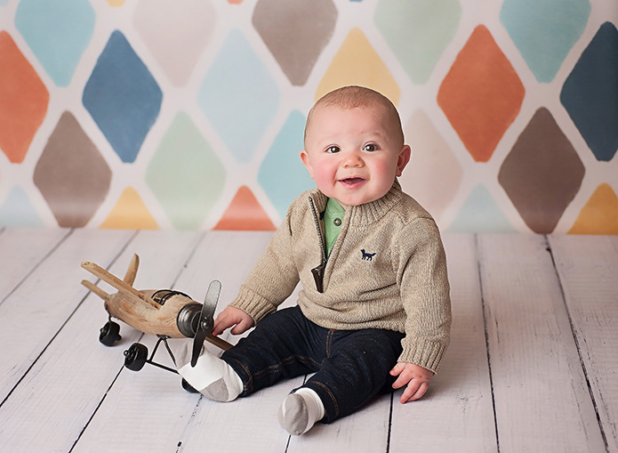 baby boy playing with wooden airplane