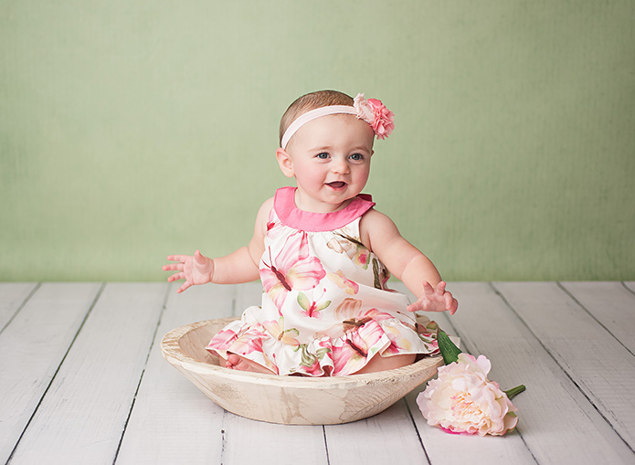 baby girl sitting in wooden bowl