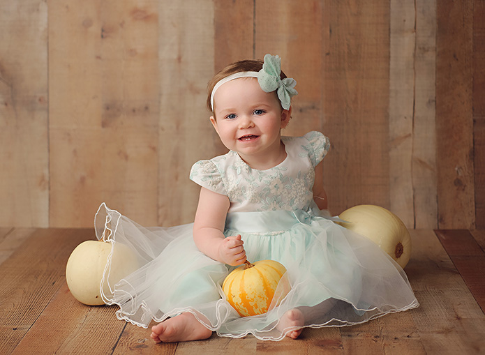 baby girl in blue dress with pumpkins