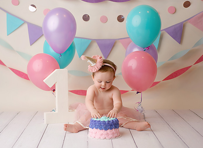 baby girl reaches for her cake during cake smash session