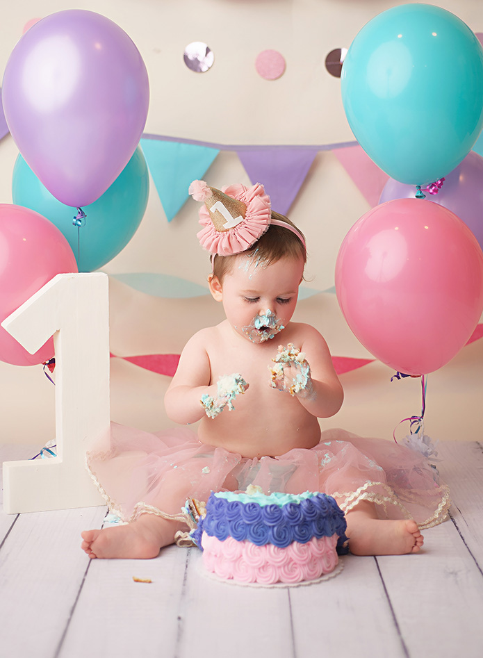 baby girl eating cake at cake smash session