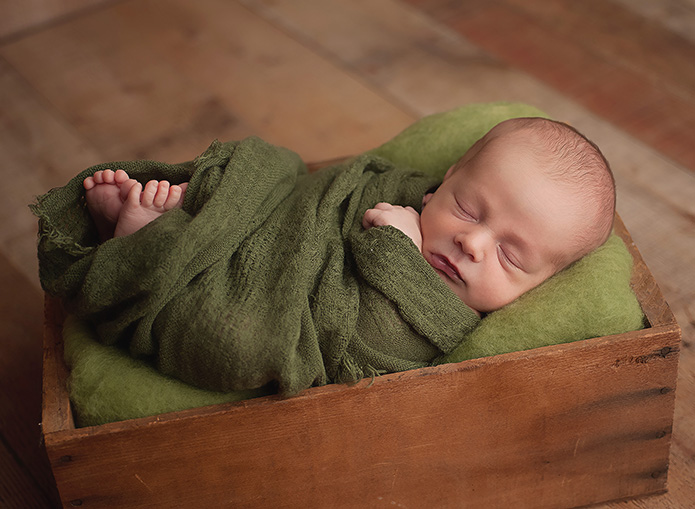 newborn boy laying in crate with green wrap