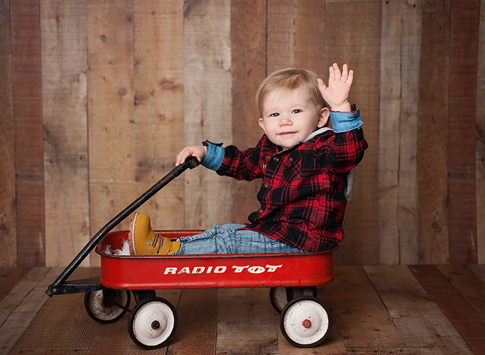 little boy sitting in a red wagon