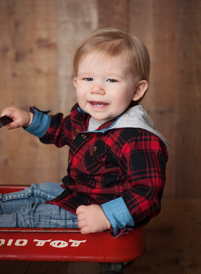 one year olf boy in red and black plaid shirt