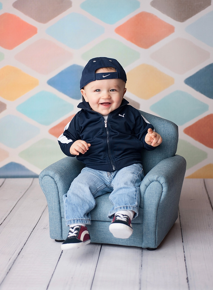 baby boy in blue hat sitting on light blue chair