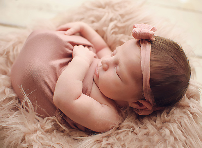 newborn baby girl wrapped in pink with pink bow