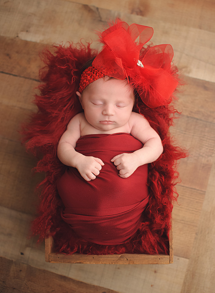 newborn girl wearing oversized red bow