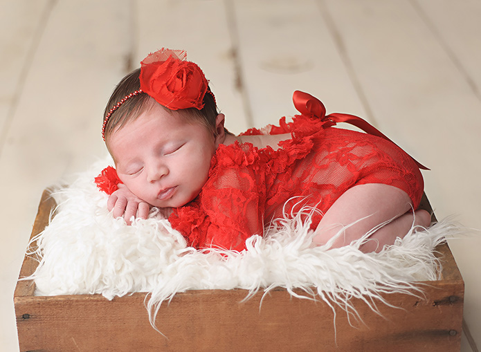 newborn baby girl with red lace romper laying on crate