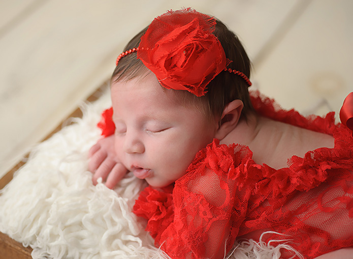closeup of newborn girls face with red headband