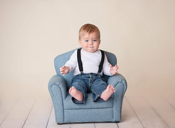 Baby boy sitting on a blue chair