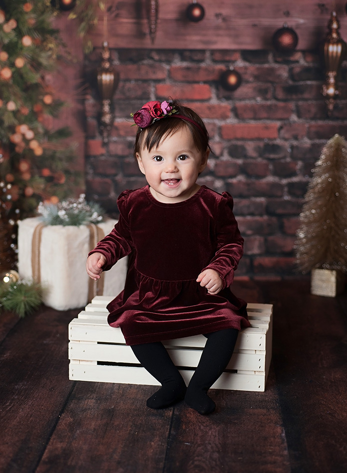 baby girl in velvet christmas dress against brick