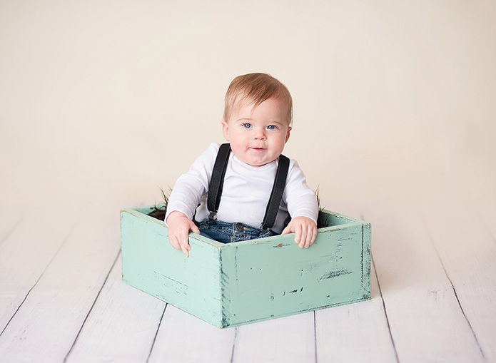 little boy sitting in blue wooden box
