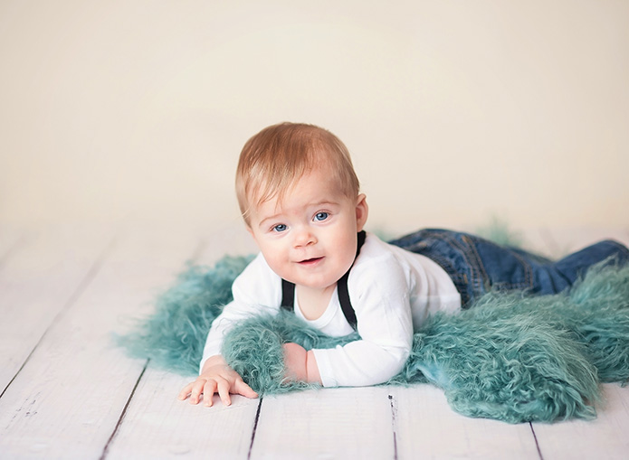 baby boy in suspenders laying on blue fur rug