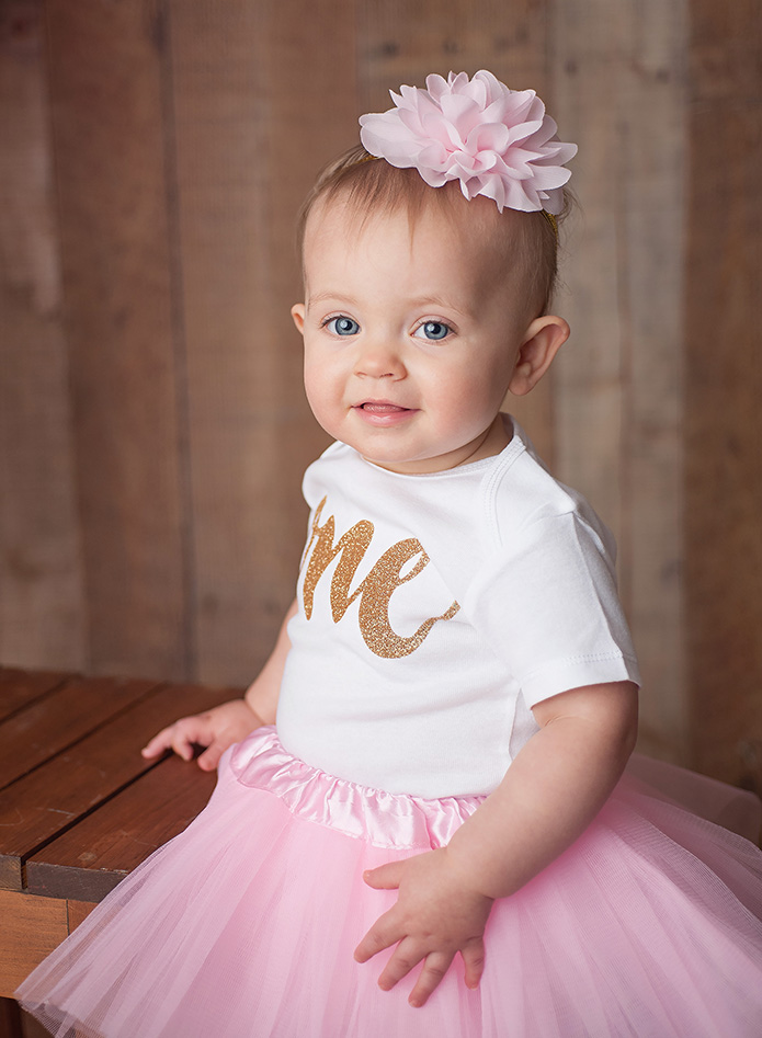 1 year old girl sitting on wooden chair in pink tutu