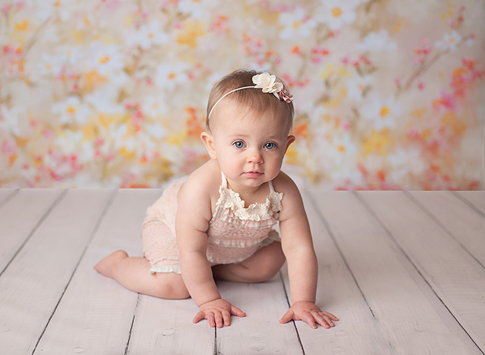 baby girl crawling away from floral backdrop