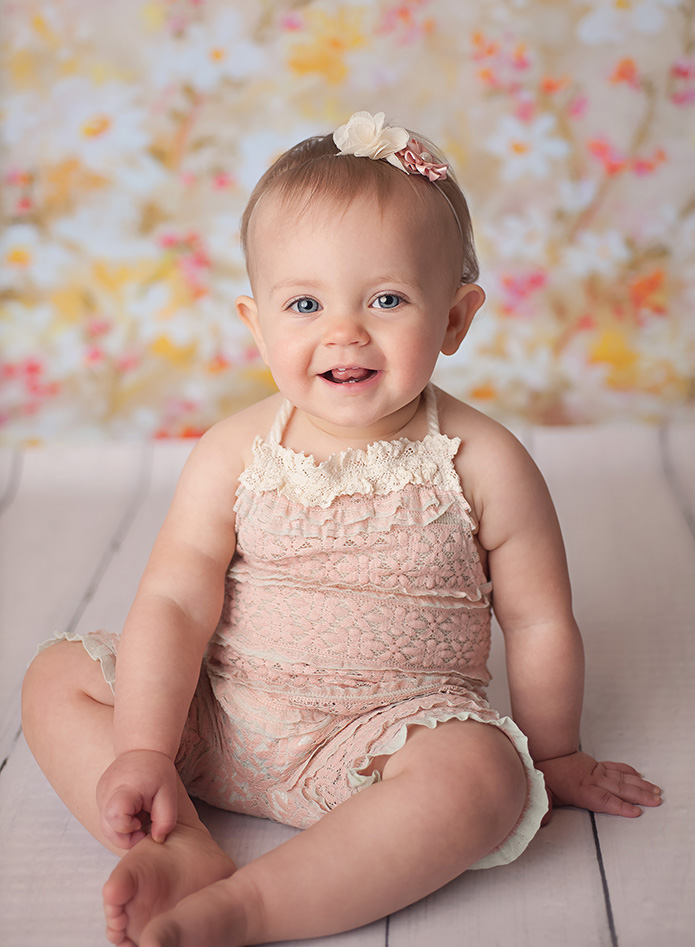 baby girl on white fur with pink romper