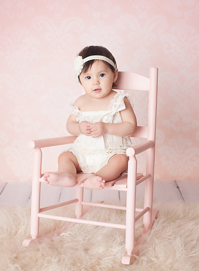 baby girl sitting in a pink rocking chair