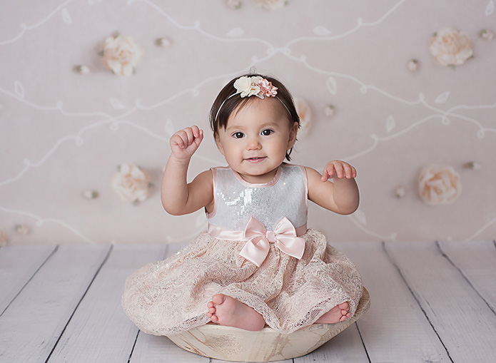 baby girl in a pink dress sitting in a white bowl