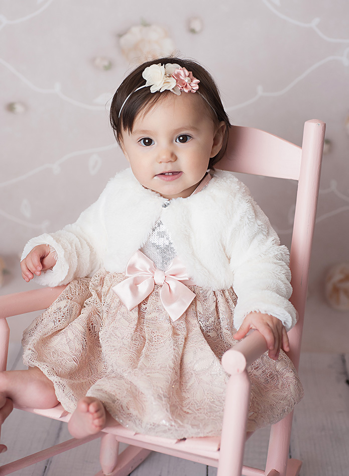 baby girl with white fur sweater on in a pink rocking chair