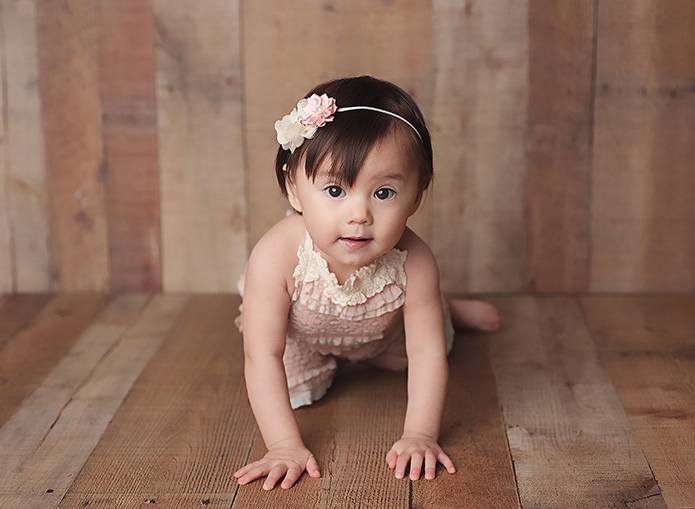 baby girl against a wooden backdrop