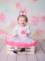 baby girl in pink and white dress