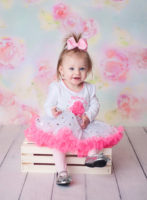baby girl with pink bow in her hair sitting on white crate