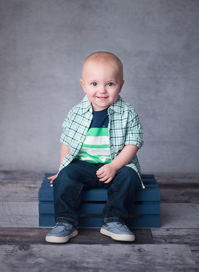 boy sitting on blue crate against grey backdrop