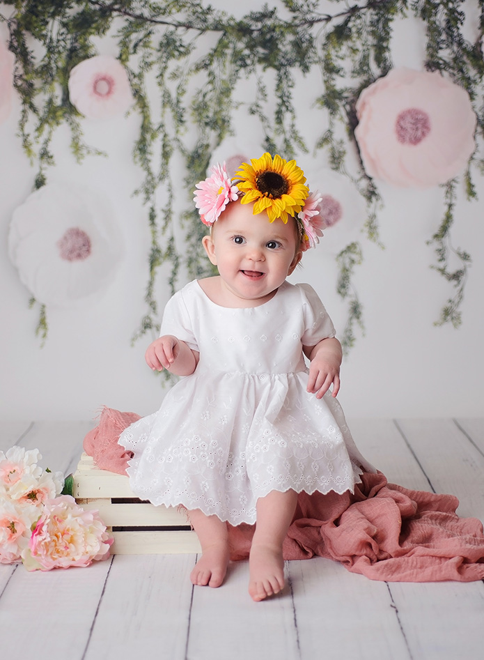 baby girl wearing floral crown sitting on white crate
