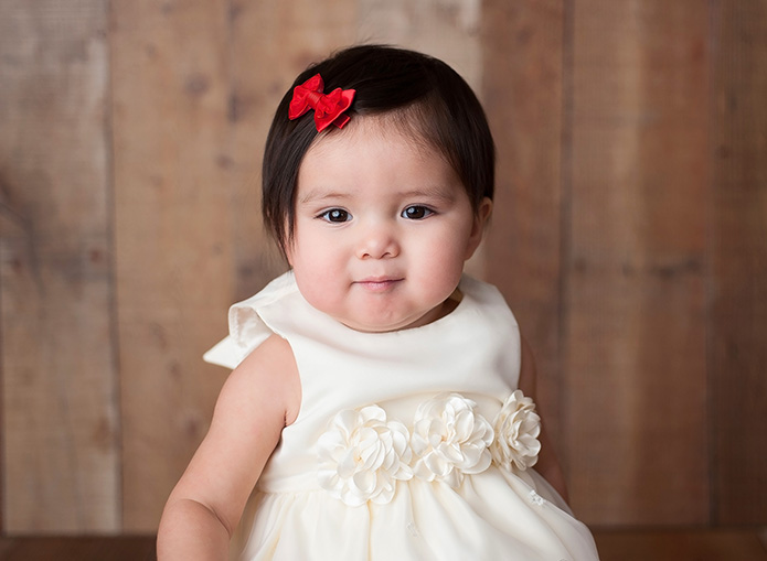 Baby girl in white dress wih red bow in hair
