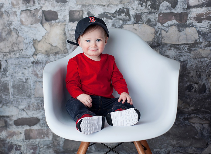 baby boy in baseball hat in red shirt