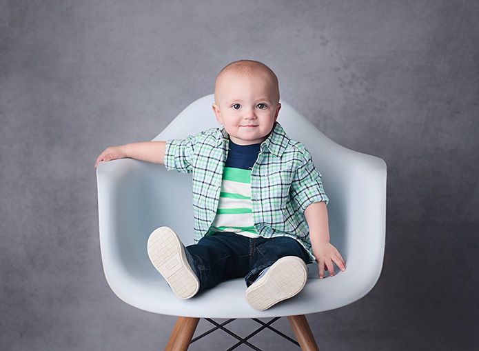 boy sitting on white chair against grey backdrop
