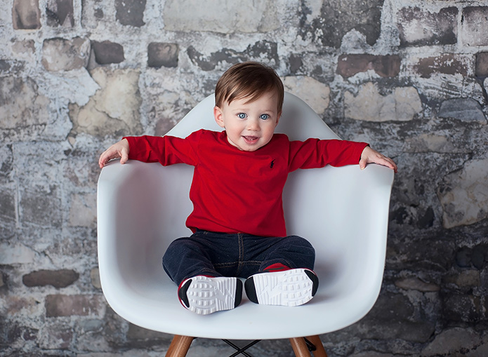 boy sitting on white chair against rock wall