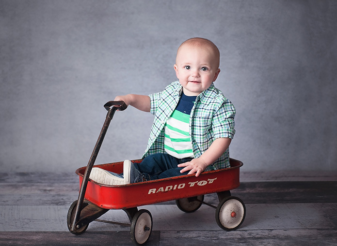 boy sitting in red wagon against grey backdrop