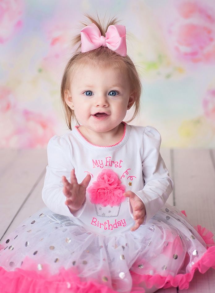 baby girl against pink floral backdrop