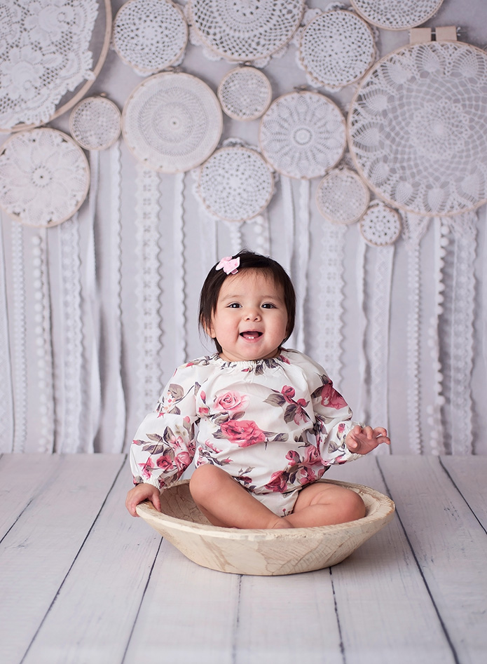 baby girl sitting in white wooden bowl