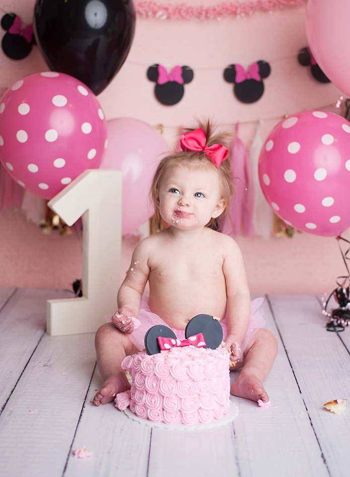 baby girl in pink tutu eating cake