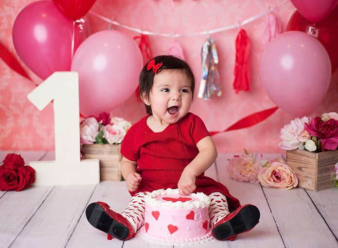 baby girl eating red and pink cake