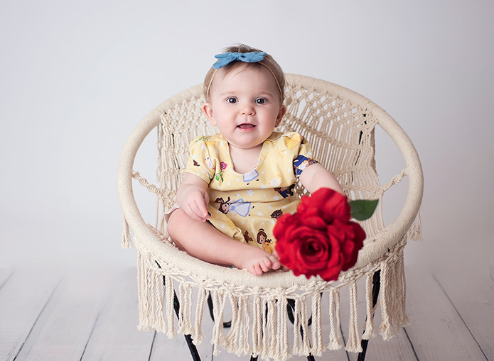 baby girl in beauty and the beast dress holding red rose