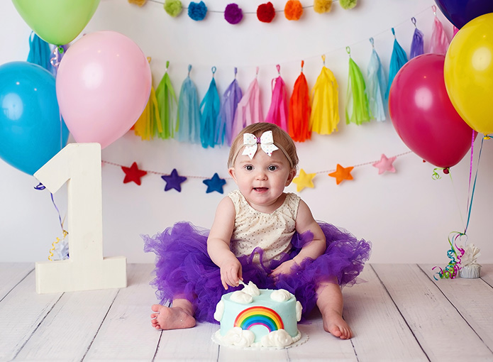 rainbow themed cake smash wih smiling baby in front of backdrop