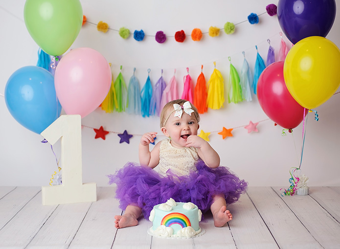 rainbow themed cake smash, baby eating cake