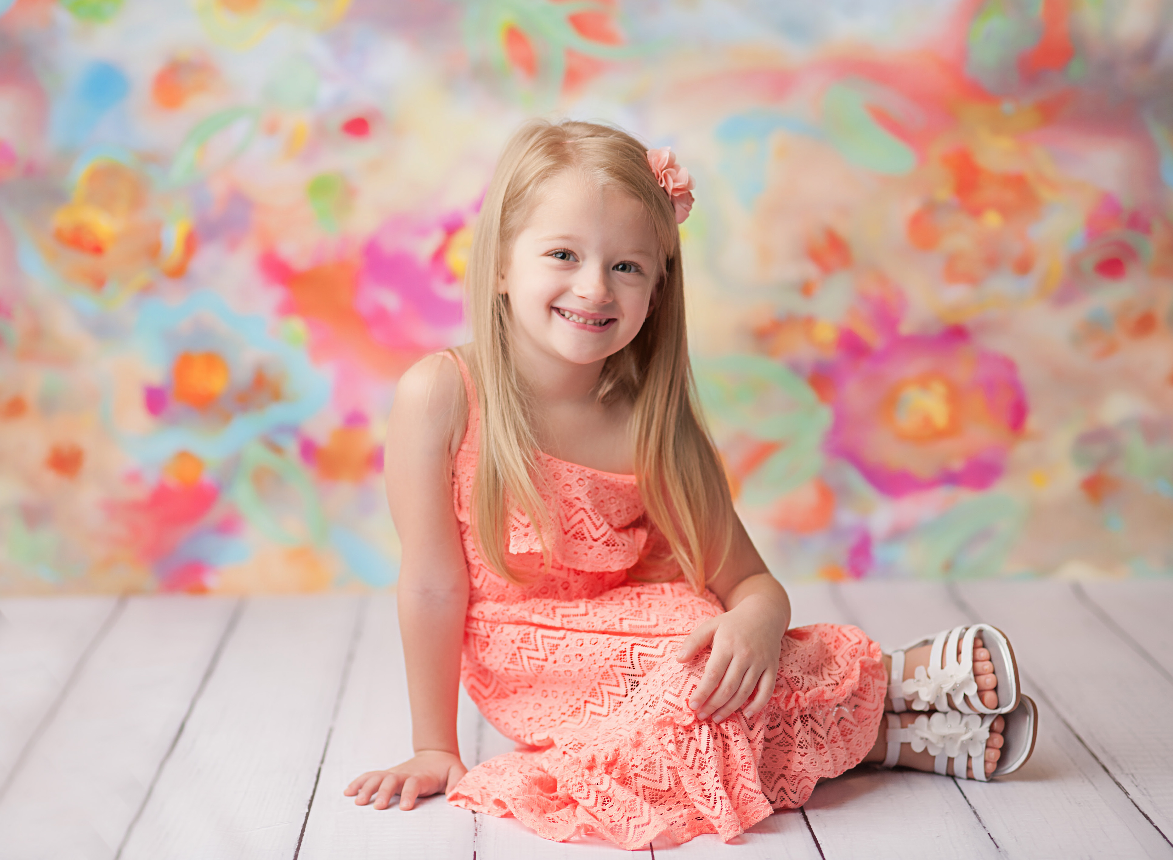 girl sitting against bright floral backdrop