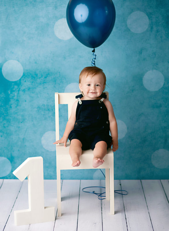boy sitting on chair with balloon