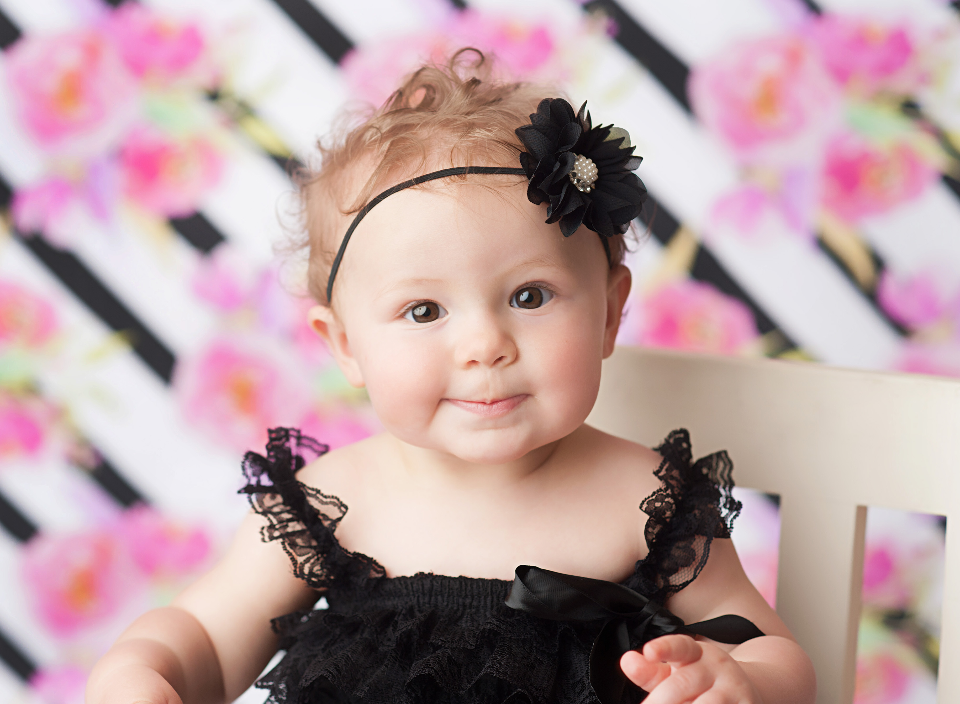 closeup of baby in black romper on floral backdrop