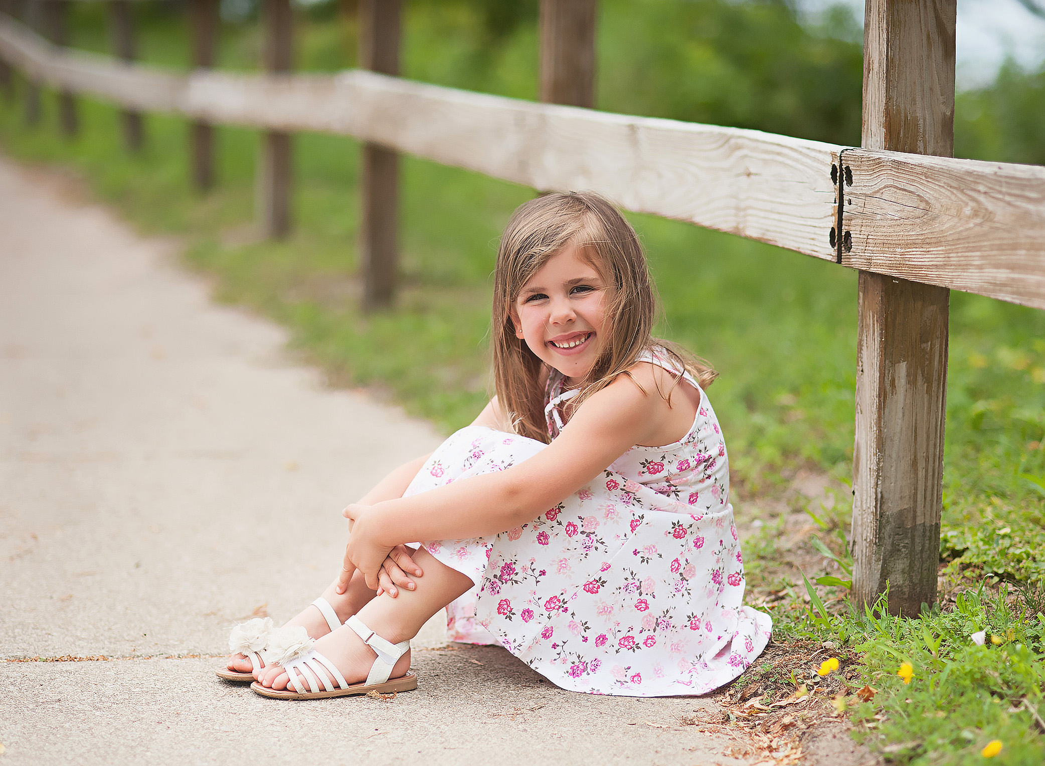 little girl sitting by a wooden fence