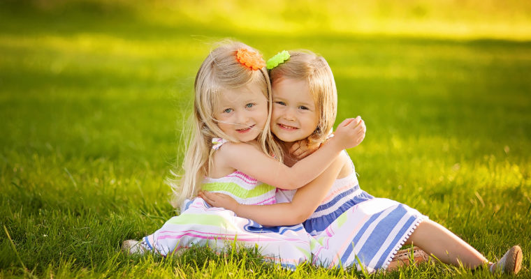 twin girls hugging in the sunlight