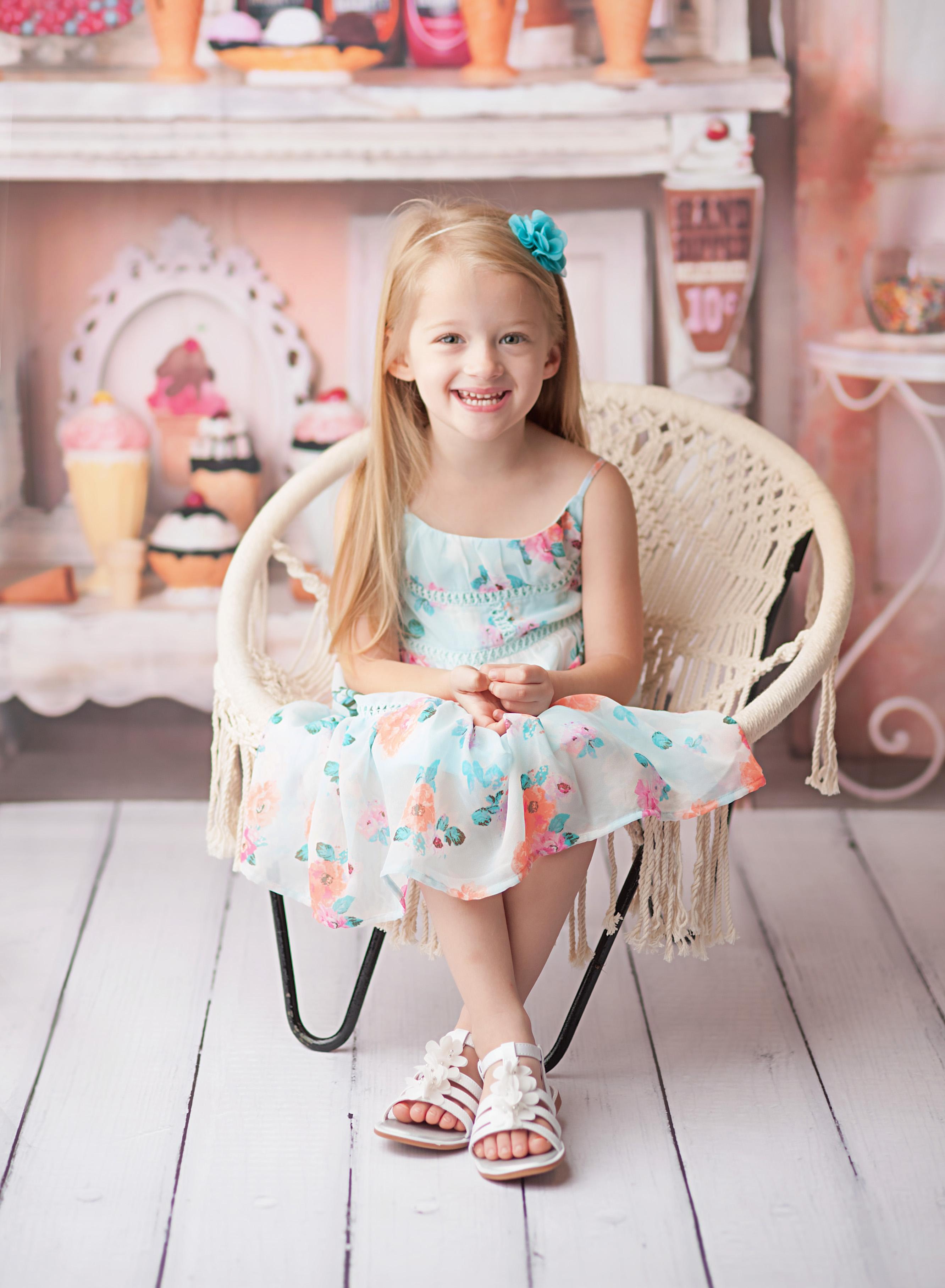 girl sitting in chair against ice cream backdrop