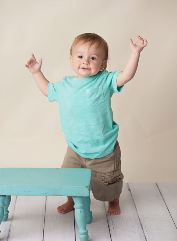 boy standing up in teal shirt