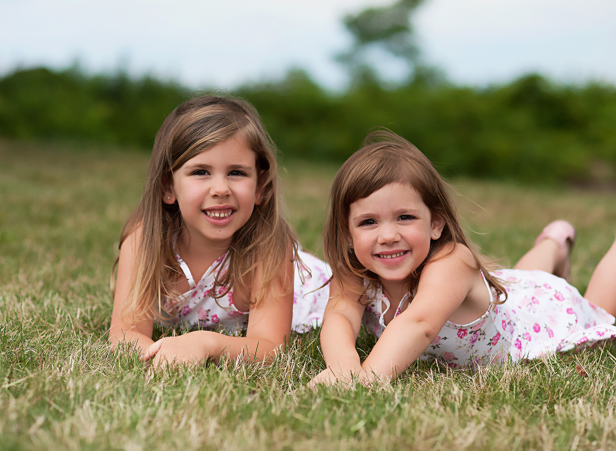 sisters laying in a field